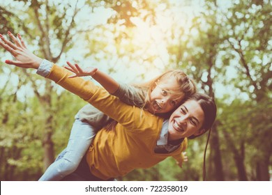 Mother and daughter outdoors in a meadow. Mother carrying her daughter on piggyback.