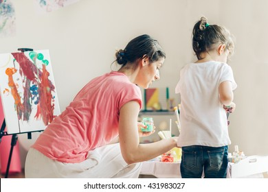 Mother and daughter painting and having great time. Selective focus and small depth of field.