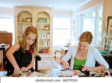 Mother and daughter pasting a collage together in their family room at home