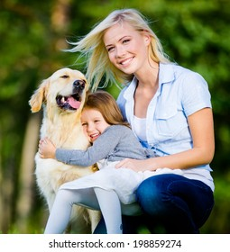Mother and daughter with pet sitting on the green grass at the summer park