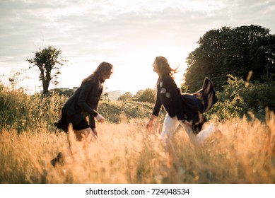 Mother and daughter photographed holding hands on the background of the sun and the sky