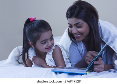 Mother and daughter with picture book in bed