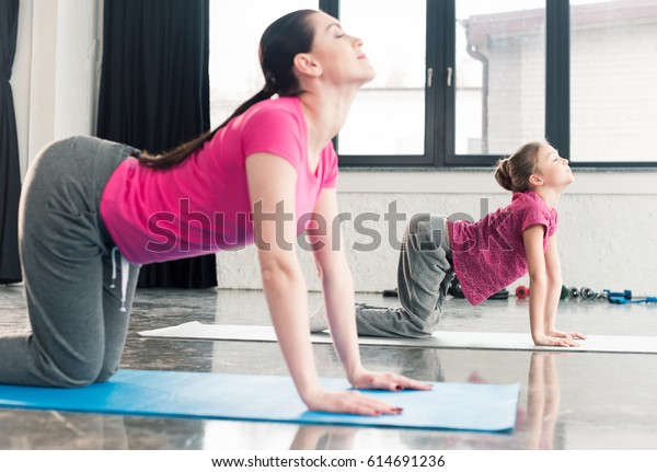 mother and daughter in pink shirts practicing yoga in Cat pose in gym