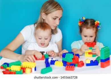 Mother and daughter play , build from the designer. Cute mom and her kids play together indoors.  Family portrait on blue background