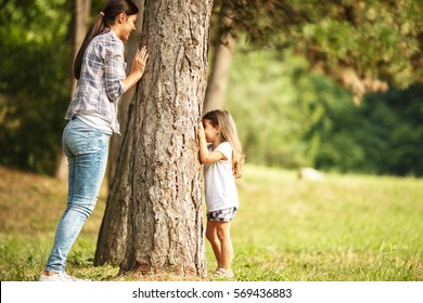 Mother and daughter play hide and seek at the park.