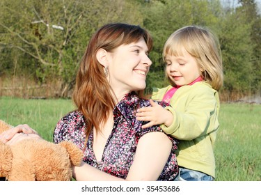 Mother and the daughter play on a meadow grass in park