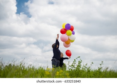 Mother and daughter playing with balloons.