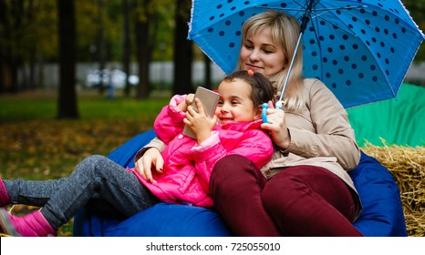Mother and daughter playing in beautiful autumn park