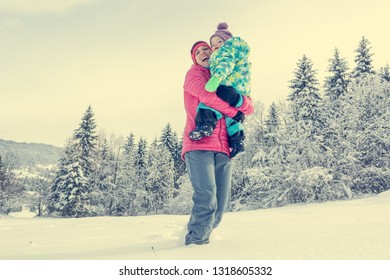 Mother and daughter playing in fairytale winter landscape.