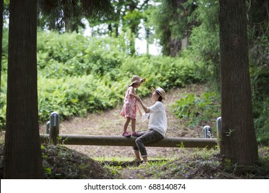 Mother and daughter playing in the forest