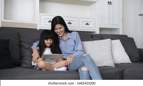 Mother and daughter are playing games together in the house.