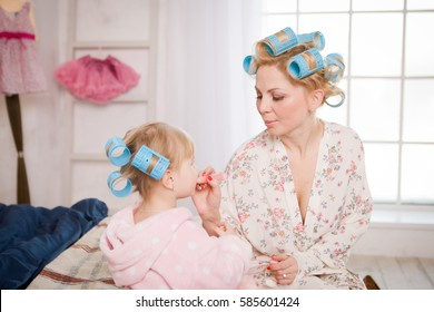Mother and daughter playing. Girl in pajamas sitting on bed and painting each other. On the head wound on the hair curler. Home morning mother and daughter