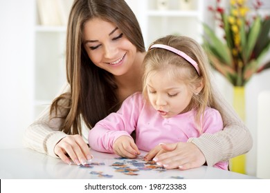 Mother and daughter playing at home. They assembling Jigsaw Puzzle.