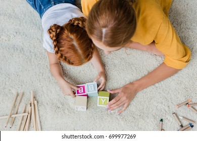 mother and daughter playing with letter cubes on floor at home