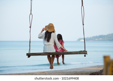 Mother and daughter playing on the beach swing