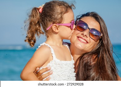 Mother and daughter playing on the beach at the day time. Concept of friendly family.