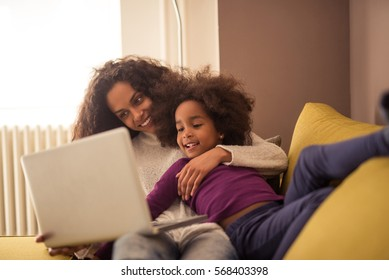 Mother and daughter playing on a computer indoors.