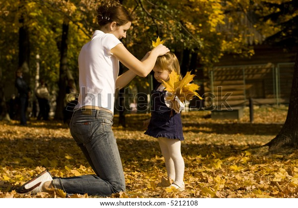 Mother and the daughter playing on fallen down leaves