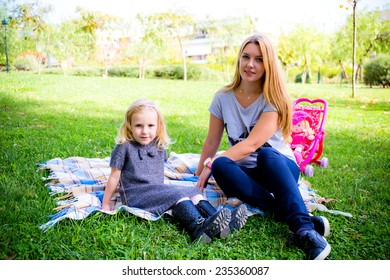 mother with daughter playing on the grass
