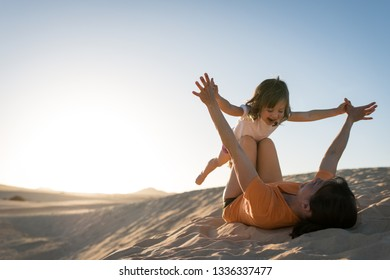 Mother and daughter playing on the sand dunes - during sunset.