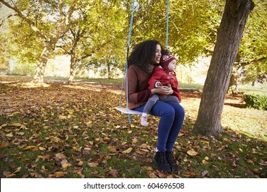 Mother With Daughter Playing On Tree Swing In Autumn Garden