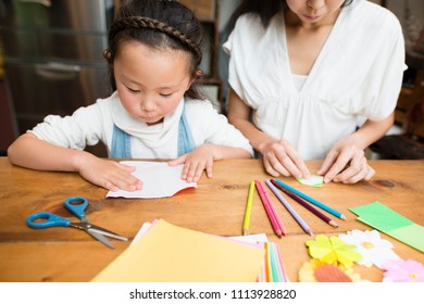 Mother and daughter playing with origami