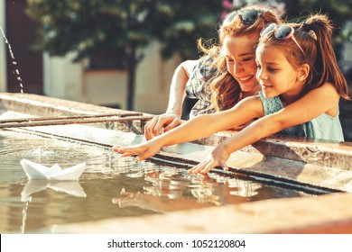 Mother and daughter playing with paper boats in the fountain in they garden.