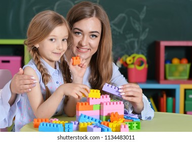 Mother and daughter playing with plastic blocks