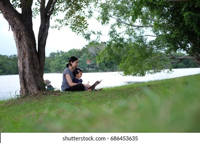 mother and daughter playing and reading at a park