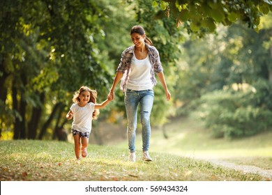 Mother and daughter playing and running around the park on beautiful morning. - Shutterstock ID 569434324