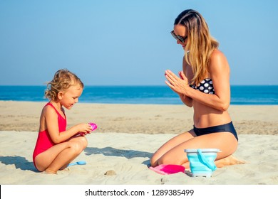 mother and daughter playing in the sand and building a sand castle on the beach