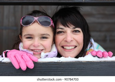 Mother and daughter playing snow