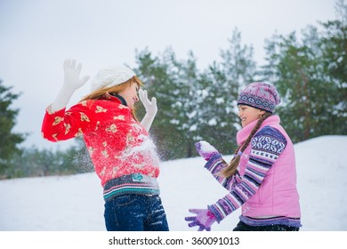 Mother and daughter playing in snow. blur, views of girls through the snow. happy family mother and daughter playing in winter