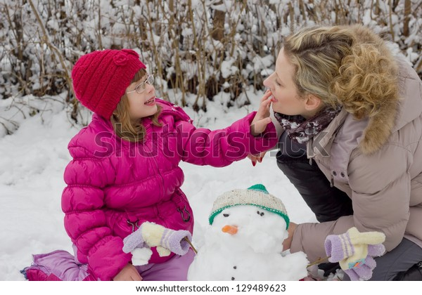 mother and daughter playing in the snow,best focus on the hair and lips mothers