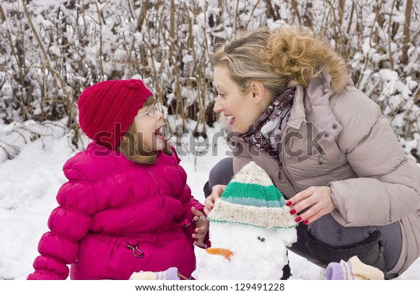 mother and daughter playing in the snow,soft focus