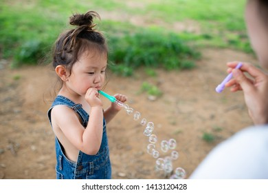 Mother and daughter playing with soap bubbles