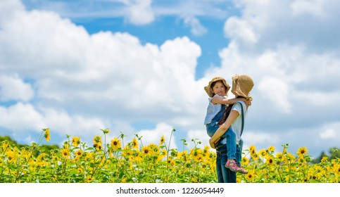 Mother and daughter playing in a sunflower field