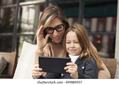 Mother and daughter playing with tablet