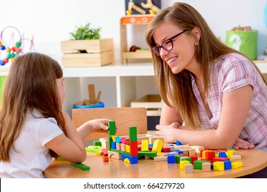 Mother and Daughter Playing Together with colorful building toy blocks. Support your child.
