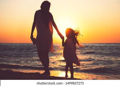 Mutter und Tochter spielen bei Sonnenuntergang zusammen am Meeresstrand.