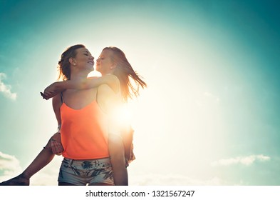 Mother and daughter playing together outdoor - Happy family piggyback at sunset - Parenthood, childhood, love and happiness concept
