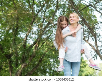 Mother and daughter playing together in  the park. Happy family concept.