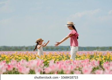 Mother and daughter playing in a tulip field