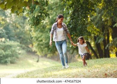 Mother and daughter playing and walking around the park on beautiful morning.