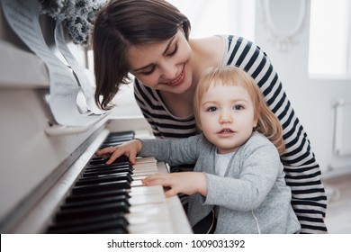 mother and daughter playing white piano, close up wiew.