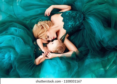 Mother and daughter. Portrait of a beautiful young mother with a cute blonde daughter dressed in elegant green dresses.