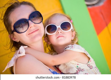 Mother and daughter portrait with colorful Caribbean house on background