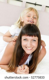 Mother and daughter posing happily in bed. Shallow DoF. Focus on mother.