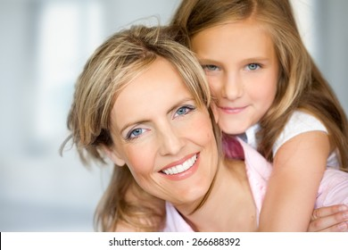 Mother and daughter posing happily on blue fuzzy background. Focus on mother.