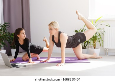 Mother and daughter practicing online yoga lesson at home at quarantine isolation period during coronavirus pandemic. Family doing sport together online from home. Healthy lifestyle